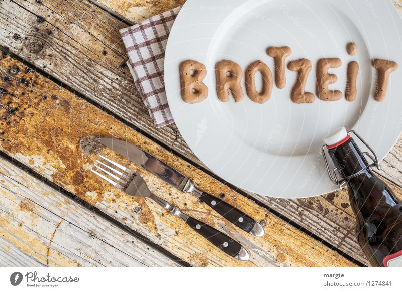 On a rustic wooden table a plate with the letters BREAD TIME, knife and fork, napkin and a bottle of beer in landscape format Food Bread Nutrition Dinner Picnic