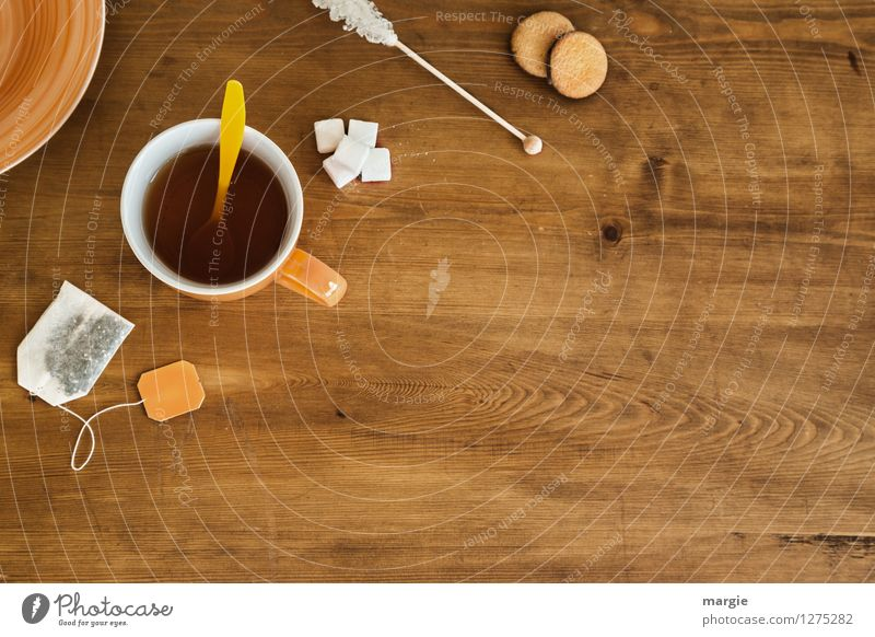 Tea- Time: a tea cup with tea bag, sugar and cookies on a wooden table Food Dough Baked goods Cake Dessert Candy Teabag Sugar Cookie Nutrition Organic produce