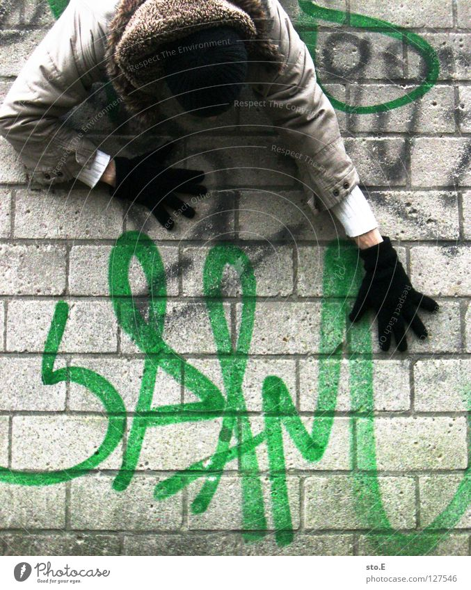 Human being Man Hand Green Black Relaxation Wall (building) Graffiti Wall (barrier) Characters Climbing Advertising Jacket Cap Traffic infrastructure Hang