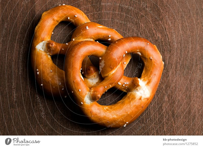 Bavarian pretzel on a brown background Food Dough Baked goods Nutrition Eating Oktoberfest Munich Germany Feasts & Celebrations eat cheers invitation bavarian