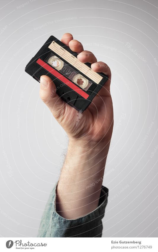 Hand holds a music cassette from the 80s in the air Lifestyle Style Design Joy Beautiful Night life Party Event Music Club Disco Bar Cocktail bar Disc jockey