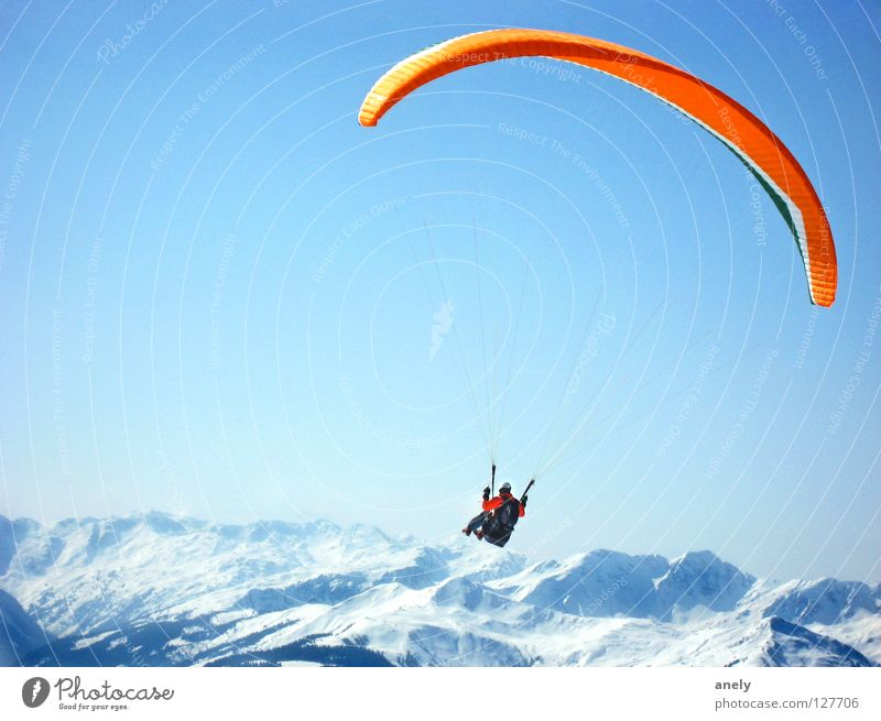 flight Paragliding Parachute Winter Panorama (View) Peak Glide Vantage point Austria Air Fantastic Paraglider Joy Extreme sports Mountain Freedom Blue sky Snow