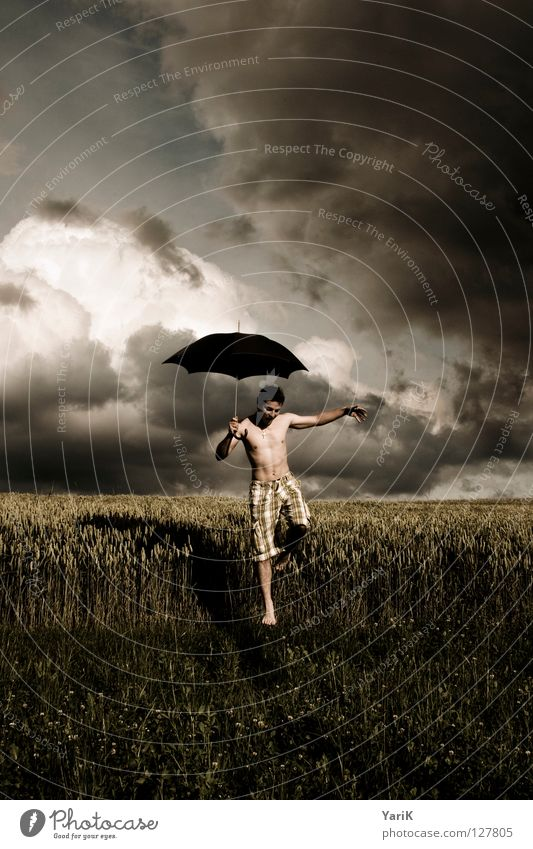 rainmaker Grass Wheat Leaf Horizon Gray Brown Yellow Dark Black Contentment Man Upper body Barefoot Pants Shorts Passion Wind Umbrella Hover Clouds Field Wet