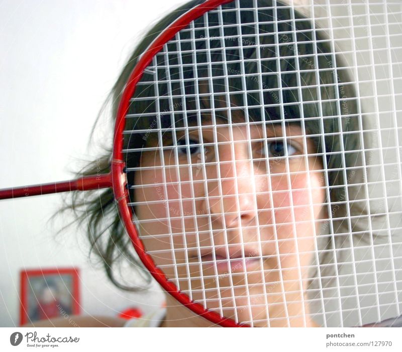 Face of a young woman hiding behind a featherball bat. Repeating the colour red. Sports grouch. Unsportsmanlike. Defense badminton rackets Sports equipment