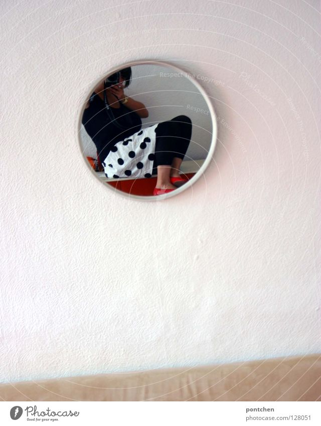 Fashion Young woman in a skirt with dots photographs herself in the mirror. Apartment Mirror Round Living room Mirror image Wall (building) White Clothing Style