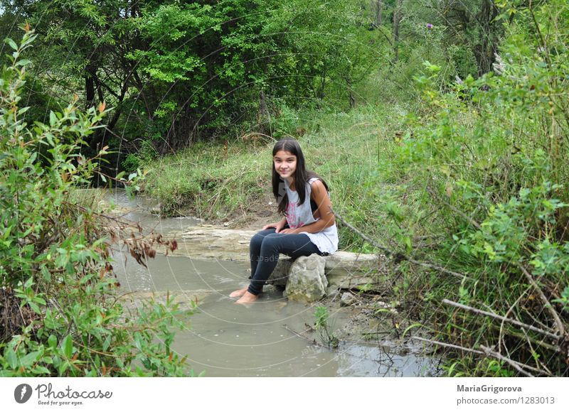 Smiling young girl stands on the river bank Lifestyle Elegant Healthy Playing Children's game Summer Summer vacation Sun Mountain Human being Feminine Girl