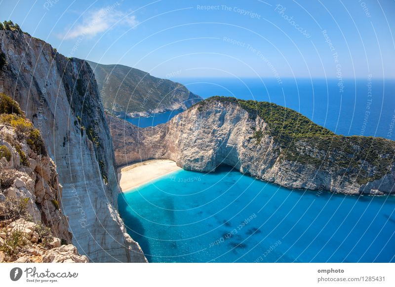 Deserted sunny beach in a sea bay. Panoramic seascape from high position of a beautiful coastal place with deep blue sea water, sun light and wide blue sky.