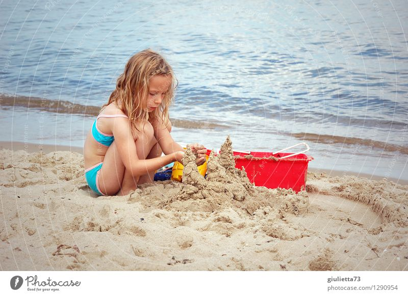 Building sandcastles by the sea Leisure and hobbies Playing Children's game Sandcastle Vacation & Travel Summer Summer vacation Beach Ocean Human being Feminine