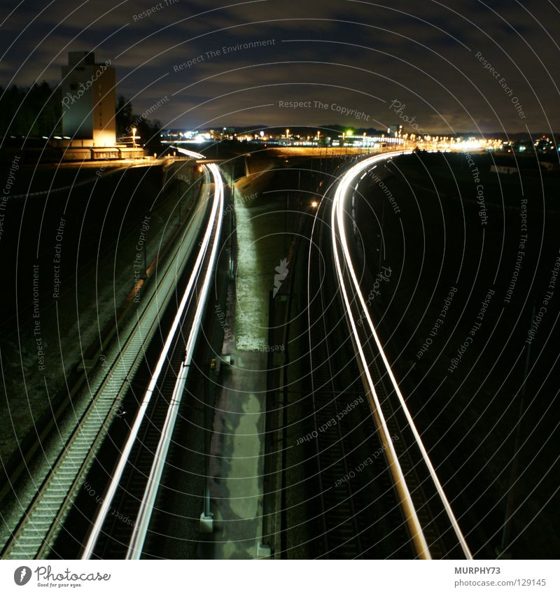 Trains at night Railroad Railroad tracks Night Long exposure Town Silo Freight car Freight train Express train Tracer path Light Clouds Tree Lamp Horizon Gray