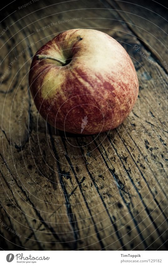 The apple in and of itself Table Tabletop Wood Wooden table Healthy Dark Kitchen Stalk Still Life Yellow Red Vitamin Meal Diet Snack Snack bar Apple skin Fruit