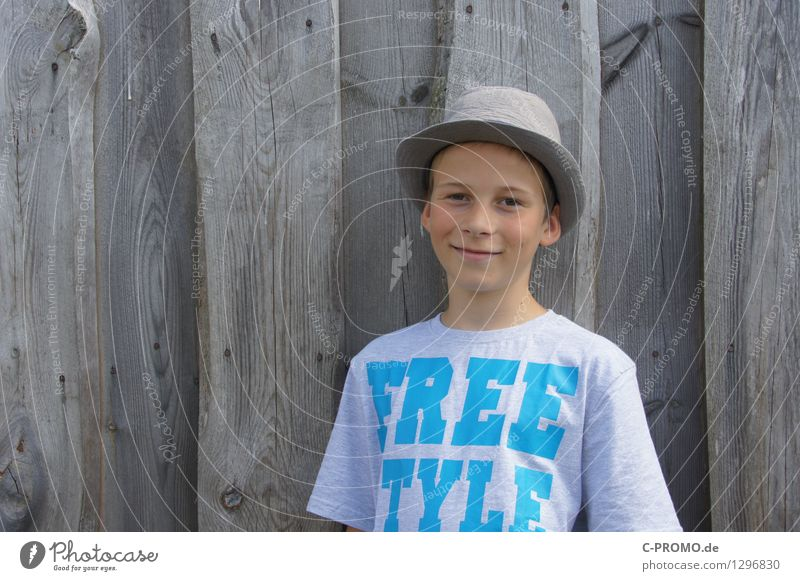 Boy with hat for wooden fence Human being Masculine Child 1 3 - 8 years Infancy 8 - 13 years Wall (barrier) Wall (building) T-shirt Hat smile Laughter Free
