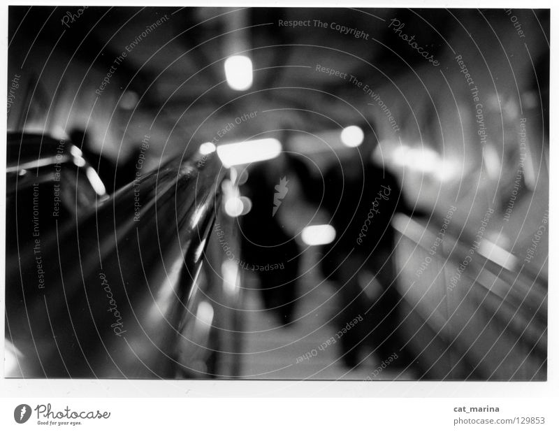 London - Tube Underground Escalator Depth of field Impersonal Dark Black & white photo Man lonely Town