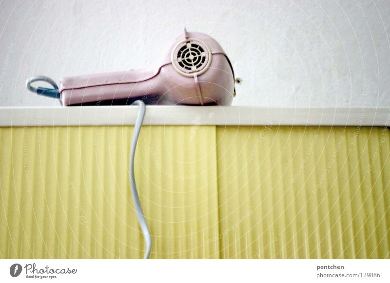 Pastels. A pink hairdryer from the 50s is lying on a yellow bathroom cabinet. Vintage, rockabilly. Style Design Hair and hairstyles Contentment