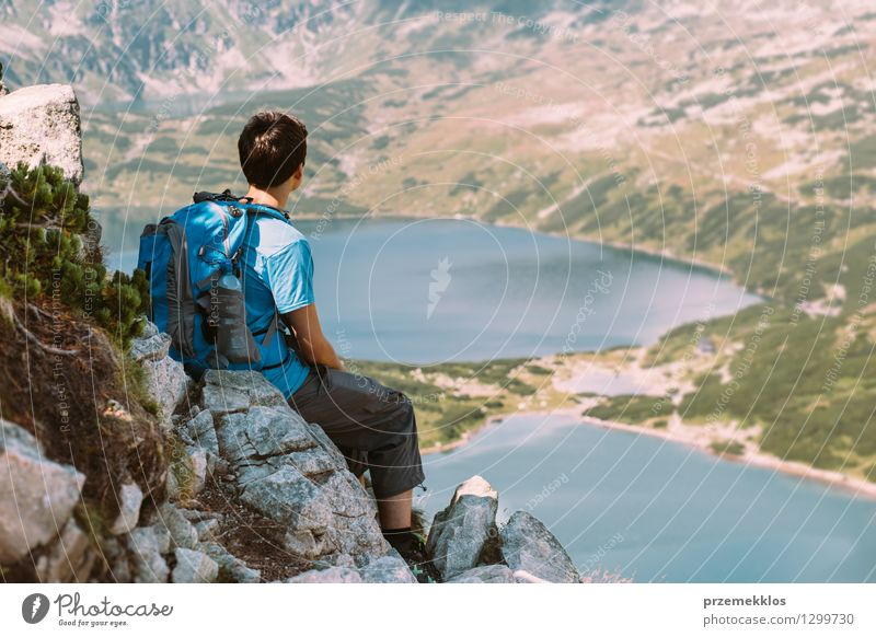 Teenager resting on rock and looking at the mountains Lifestyle Beautiful Vacation & Travel Trip Adventure Freedom Summer Mountain Hiking Boy (child) Young man