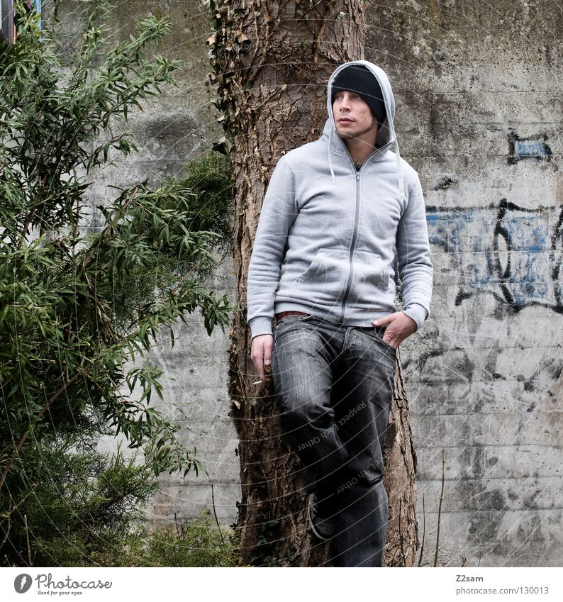 smoking break Man Youth (Young adults) Stand Smoking Cap Tree Green Bushes Style Human being Posture Hooded (clothing) tree wall Graffiti Jeans Lean Looking