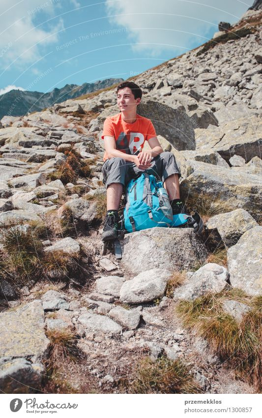 Boy resting on a rock in the mountains Lifestyle Vacation & Travel Trip Adventure Freedom Summer Mountain Hiking Boy (child) Young man Youth (Young adults) 1