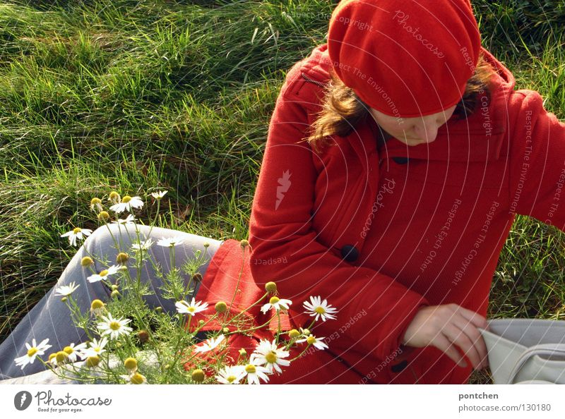 Woman dressed in red sitting on a meadow and looking for something in her handbag Looking away Trip Adults by hand Fingers Beautiful weather flowers Meadow