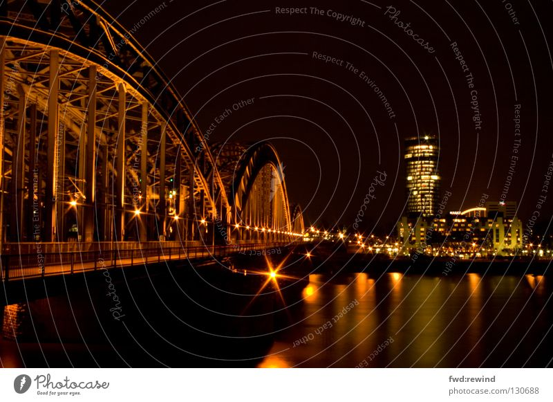 Cologne in a different way Light Night Town Long exposure Night shot Yellow High-rise Steel Railroad Bridge triangletower Skyline Gold Rhine Water Reflection