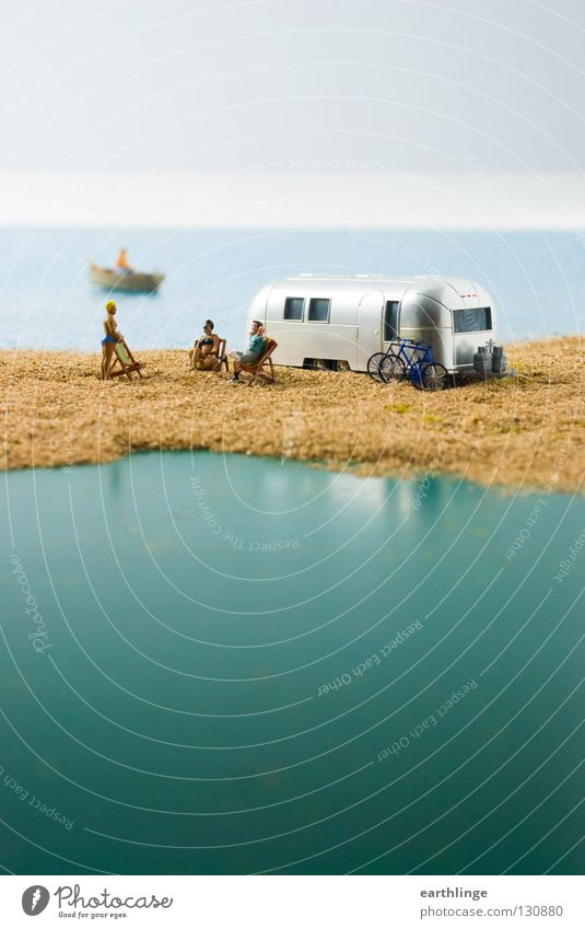 Small camper paradise Mobile home Caravan Miniature Green Deckchair Rowboat Reflection Close-up Far-off places Portrait format Digital photography Horizon Blur