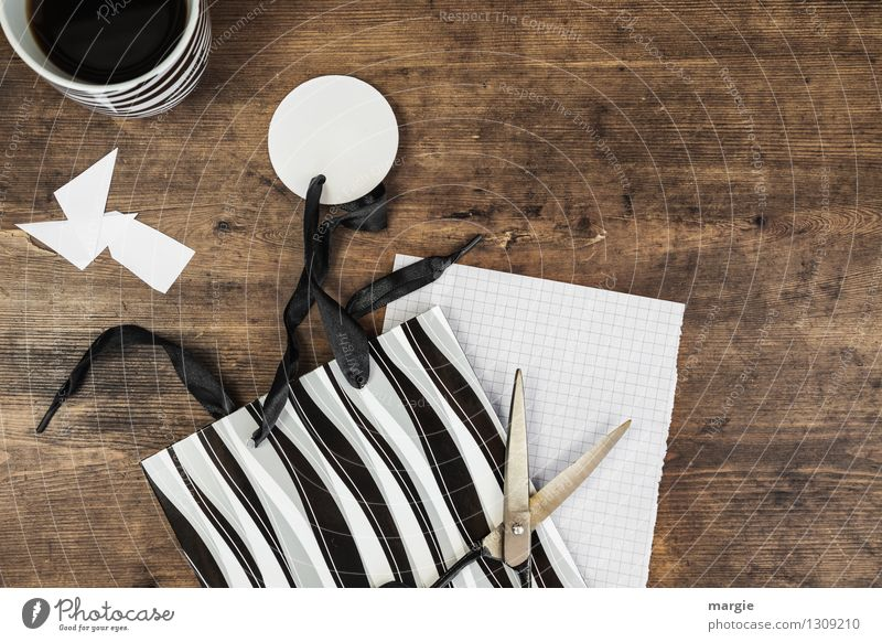 gift wrap with scissors, a black and white bag and a cup of coffee Beverage Coffee Cup Leisure and hobbies Handicraft Gift wrapping Desk Workplace Zebra