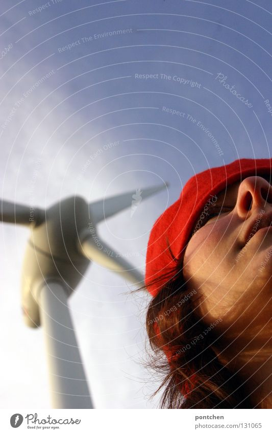 Face of a woman with red headgear in front of a windmill and blue sky Hair and hairstyles Sun Industry Energy industry Renewable energy Wind energy plant