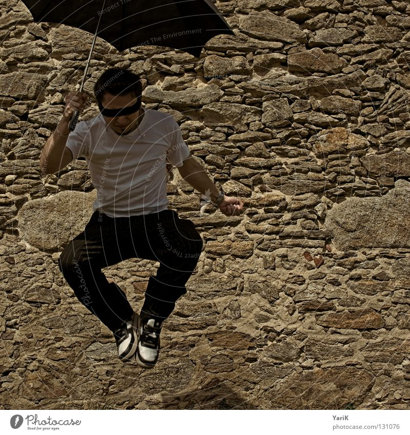 uncertain Jump Umbrella Man T-shirt White Black Brown Stony Wall (building) Wall (barrier) Stone wall Plaster Drop shadow Happiness Cheerful