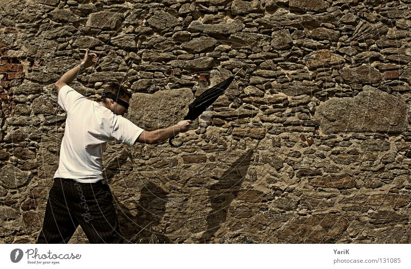 Over and out Jump Umbrella Man T-shirt White Black Brown Stony Wall (building) Wall (barrier) Stone wall Plaster Drop shadow Happiness Cheerful