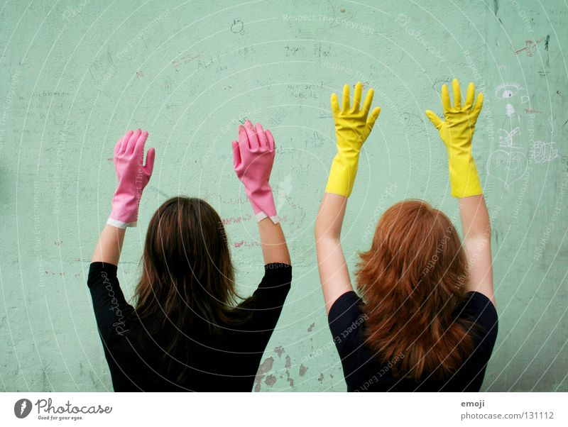 Two unidentified women wearing gloves Gloves Rubber Pink Yellow Gaudy Intoxicant Turquoise Wall (building) Hand Describe Dirty Cleaning Noble Whimsical Strange