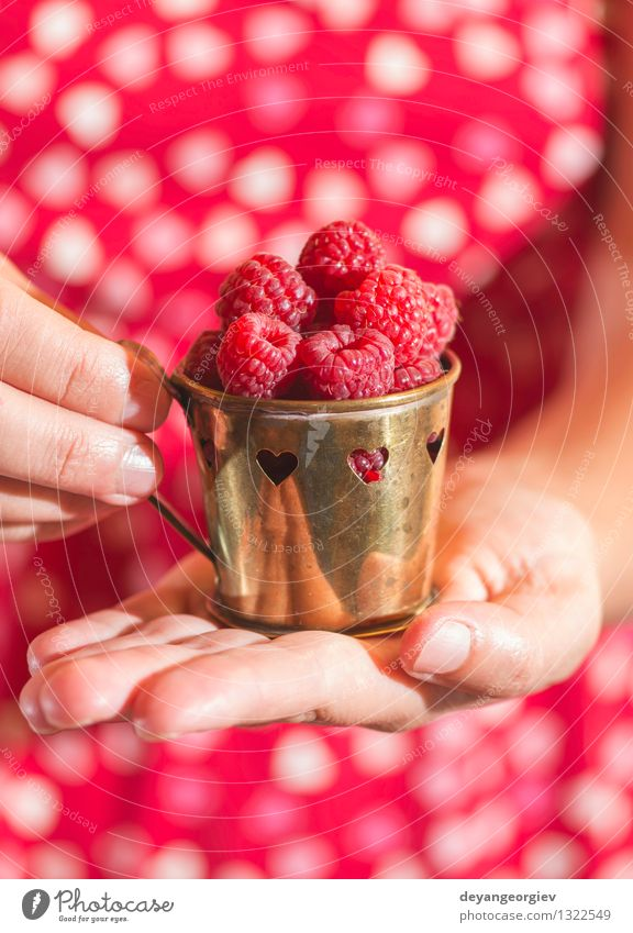 Woman in red dress holding a cup of raspberries Fruit Vegetarian diet Lifestyle Summer Garden Girl Adults Hand Heart Love Fresh Natural Green Red Romance