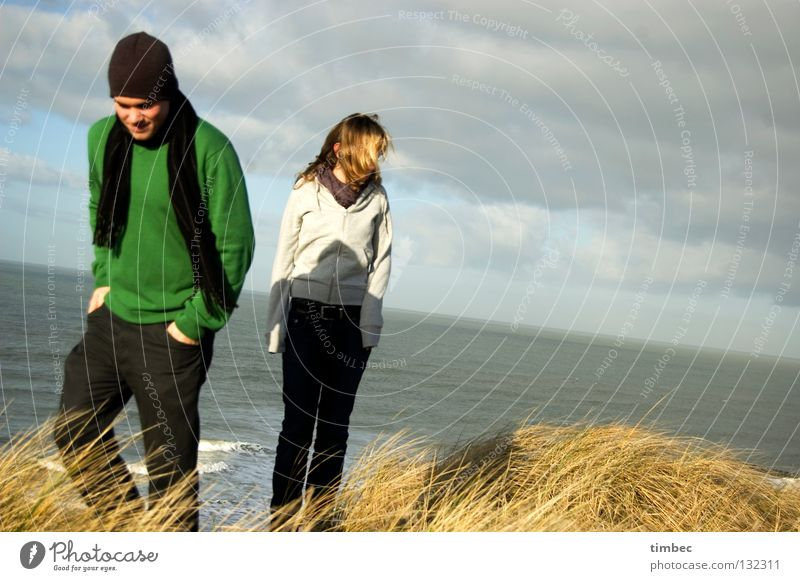 The two of us Man Woman Ocean Clouds Bad weather Beach Green Gray Sweater Scarf Cap Movement Going Grass Wind Divide Cold Hand Pants Dark Winter Human being