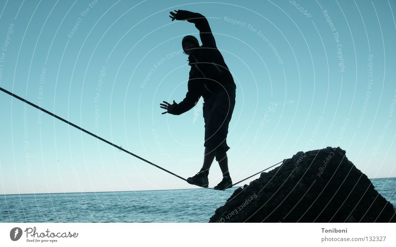 Man Hand Sky Ocean Calm Far-off places Sports Playing Contentment Coast Adults Arm Rope Rock Safety
