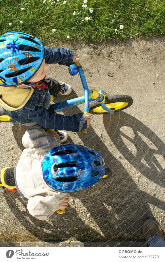 On your mark, get set, go... Child Helmet Safety Adversary Grass Meadow Bird's-eye view Playing Sporting event Competition Funsport Bicycle Shadow Beginning