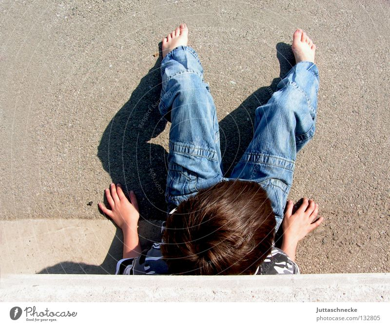 Child Relaxation Boy (child) Wall (building) Hair and hairstyles Head Wall (barrier) Wait Concrete Sit Jeans Break Peace Boredom Parking lot Barefoot