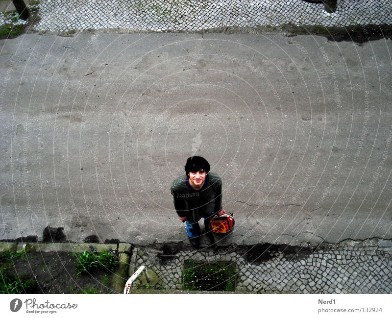 Socialist waste Street Cobblestones Paving stone Man Laughter Bucket Old Derelict Tumbledown Bird's-eye view Exterior shot Upward Copy Space middle Young man