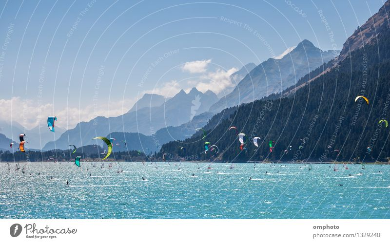 Mountain landscape with a lot of kite surfers and windsurfers moving in a lake. They use the wind to move their boards on the water. Mountains are as background in a sunny day.