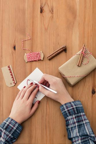 Christmas preparations Christmas & Advent Cutter Knife Feminine Arm Hand 1 Human being Clothing Stationery Paper Packaging Brown Contentment Anticipation