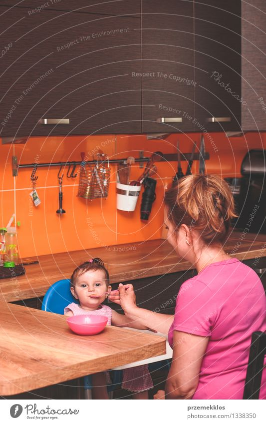 Woman feeding her little girl in kitchen Nutrition Eating Lunch Dinner Diet Lifestyle Kitchen Child Human being Baby Toddler Girl Adults Parents Mother