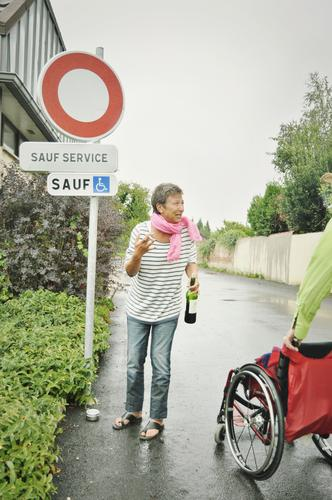 on the road again | sauf service Street Woman Wheelchair booze service French France Wordplay Alcoholic drinks bottle of wine Road sign walking impediment