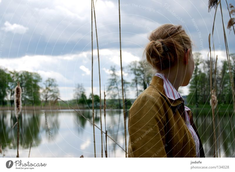 aversion Lake Woman Feminine Youth (Young adults) Mirror Tree Bushes Park Interior lake Common Reed Clouds Dreary Physics Spring Green Blouse Shirt Chignon