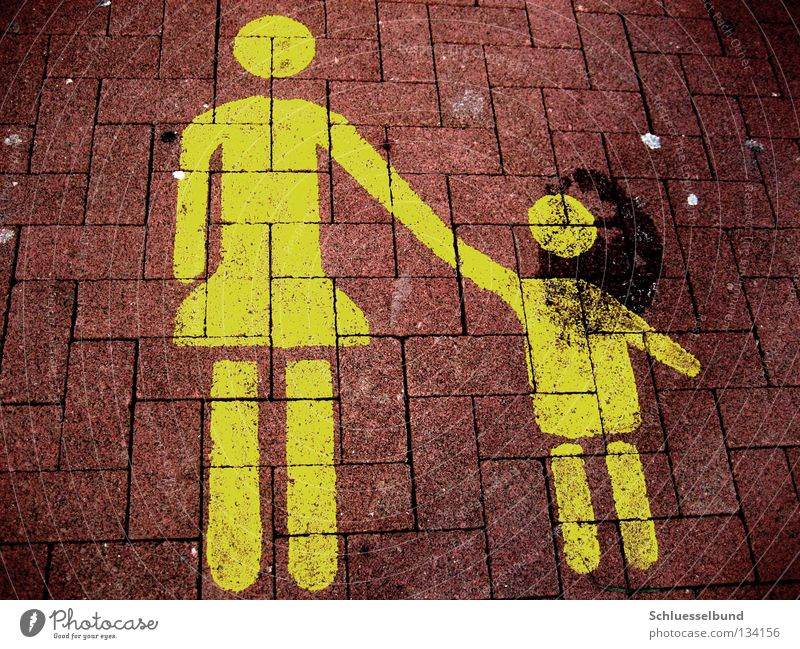 Mother with child Parking Child Adults Arm Legs Traffic infrastructure Stone Dark Yellow Red Black Lane markings Stone floor Parking lot Touch Colour photo