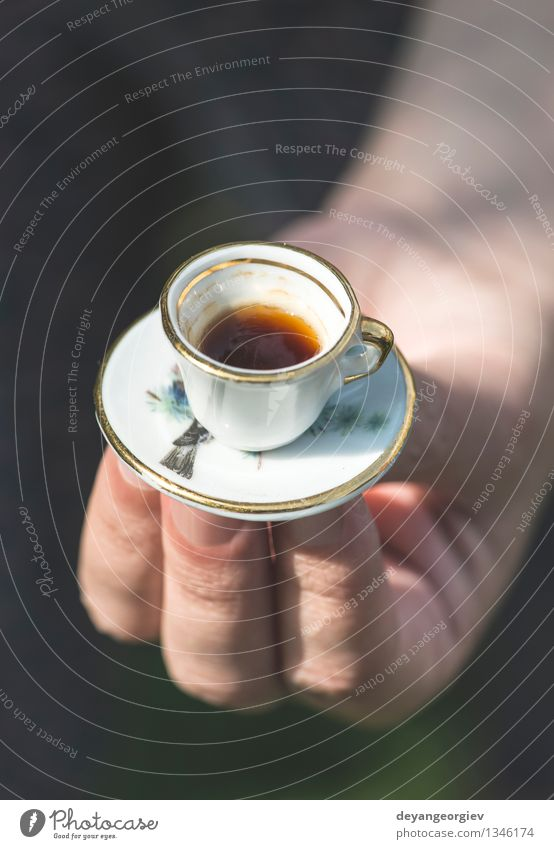 Hand hold very small cup of coffee. Coffee Style Garden Table Woman Adults Old Hot Small Retro White Colour Miniature Café Hold overhead vintage Saucer people