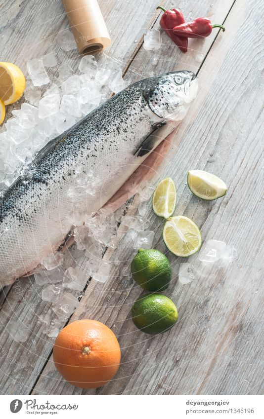 Raw salmon fish in ice and vegetables White Red Fresh Table Cooking & Baking Paper Vegetable Delicious Frozen Meal Dinner Tomato Lemon Ingredients