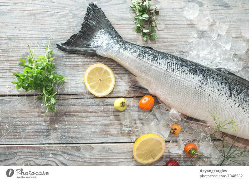 Raw salmon fish in ice and vegetables Seafood Vegetable Dinner Table Cook Paper Fresh Delicious Red White Salmon Lemon Baking paper knife wooden Tomato Broccoli