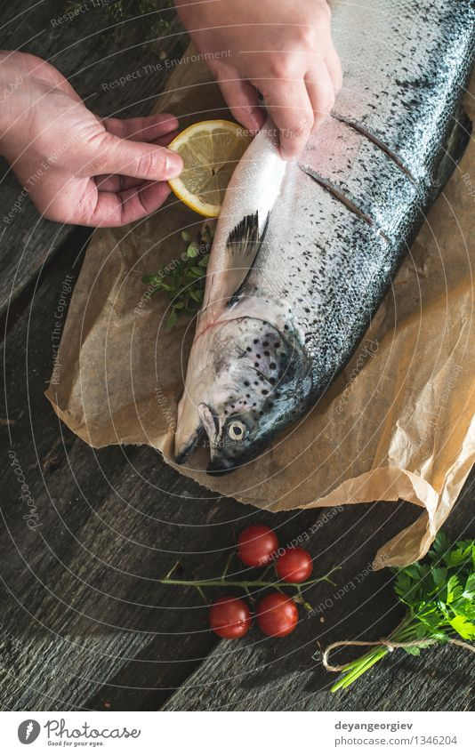 Preparing whole salmon fish for cooking. Dark Black Fresh Table Cooking & Baking Paper Rope Vegetable Delicious Meal Dinner Tomato Lemon Raw Ingredients Rustic