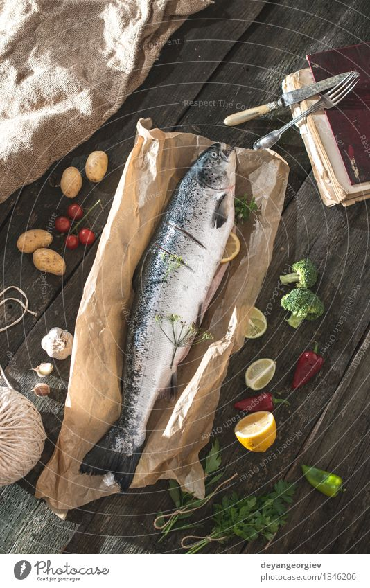 Preparing whole salmon fish for cooking Dark Black Fresh Table Cooking & Baking Paper Rope Vegetable Delicious Meal Dinner Tomato Lemon Raw Ingredients Rustic