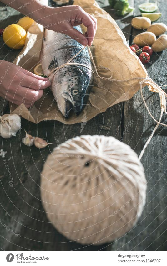 Tying a rope on fish for grilling Dark Black Fresh Table Cooking & Baking Paper Rope Vegetable Delicious Meal Dinner Tomato Lemon Raw Ingredients Rustic