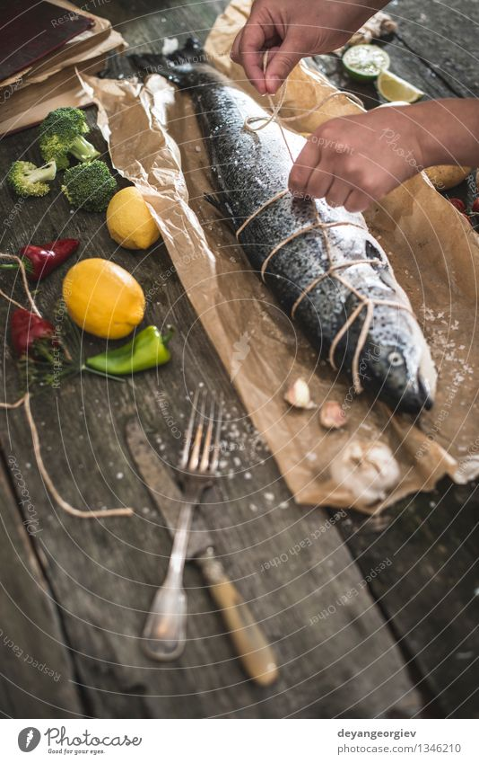 Tying a rope on fish for grilling Hand Dark Black Fresh Table Cooking & Baking Paper Rope Vegetable Delicious Meal Dinner Tomato Lemon Raw Ingredients