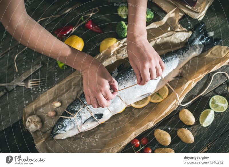 Tying a rope on fish for grilling Seafood Vegetable Dinner Table Cook Rope Hand Paper Dark Fresh Delicious Black Cooking Raw Ingredients Meal Lemon Preparation