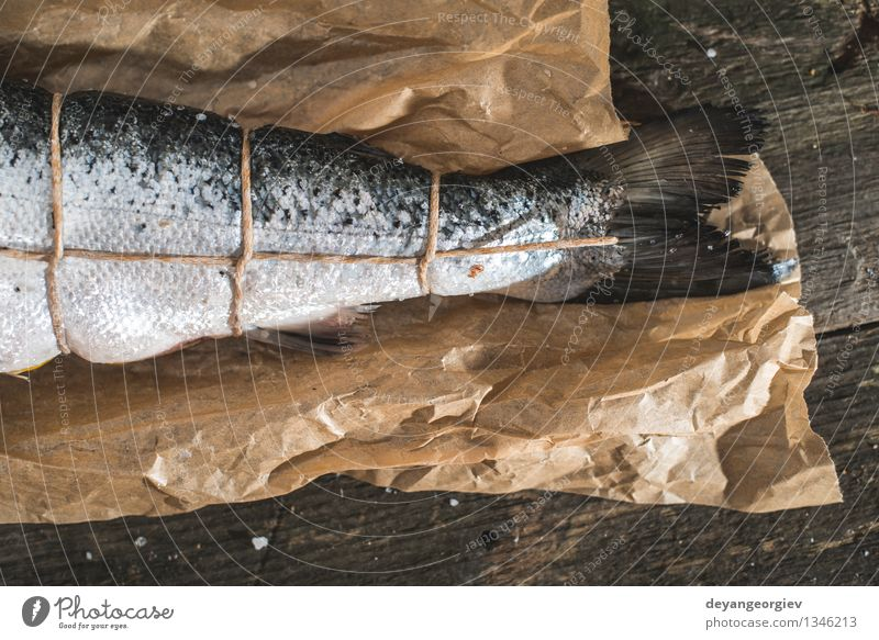 Tying a rope on fish for grilling Dark Black Fresh Table Cooking & Baking Paper Rope Delicious Meal Dinner Raw Ingredients Rustic Preparation Seafood