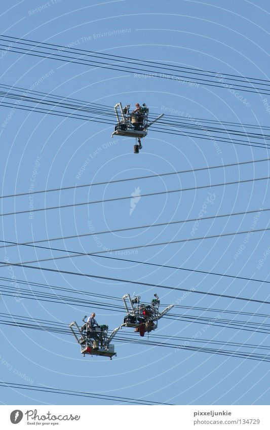 Balance Act at Airy Height Electricity Dangerous Industry Tall Level Transmission lines Blue driven Threat